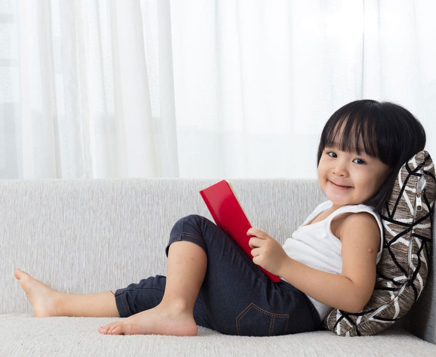 A child is sitting on the couch, reading a book and smiling.