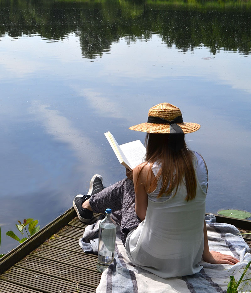 A woman is sitting on a lake and reading a book.